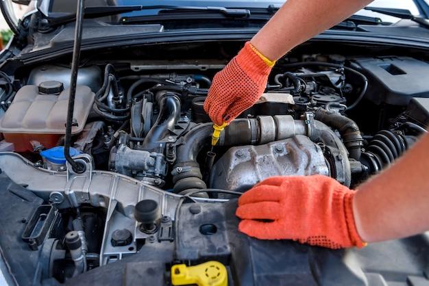 Handen van monteurs in beschermende handschoenen met motor van een auto close-up