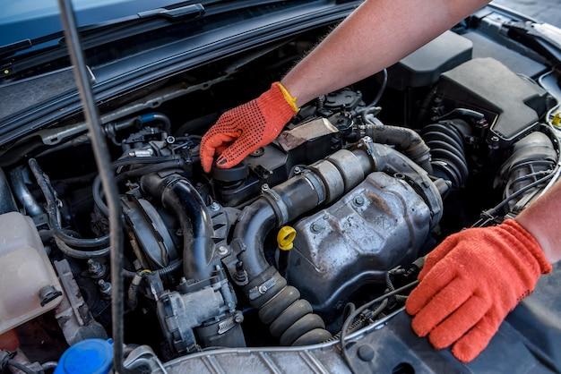 Handen van monteurs in beschermende handschoenen met motor van een auto close-up Premium Foto