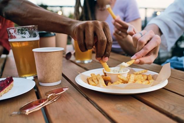 Handen van multiraciale vrienden die frietjes in pikante saus zetten