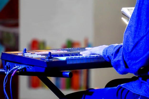 Handen van musicus die een elektronisch toetsenbord op stadium met blauwe verlichting speelt