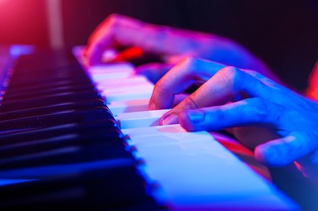 Handen van muzikant toetsenbord bespelen in concert met ondiepe scherptediepte