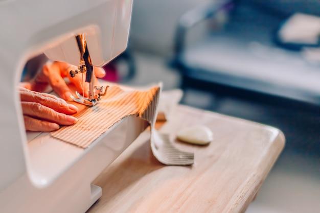 Handen van naaien proces. vrouwelijke handen die stof op machinehobby thuis stikken