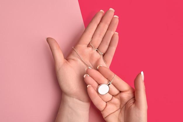 Handen van onbekende jongedame houden blanco hanger van glanzend zilver of platina vast