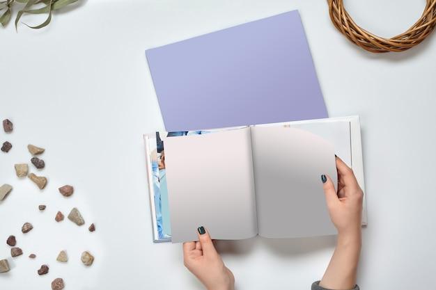Handen van onbekende vrouw die open fotoboek met harde kaft en blanco pagina's vasthoudt