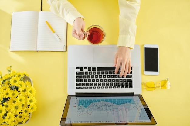 Handen van onderneemster die kop hete zwarte thee drinkt en aan laptop thuis werkt