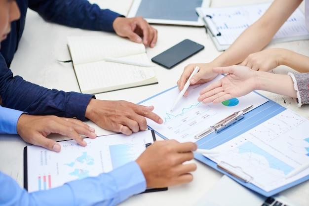 Handen van ondernemers die naar grafiek in financieel verslag op tafel wijzen en bedrijfsontwikkeling bespreken