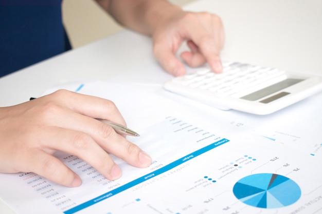 Handen van ondernemers werken op het bureau met behulp van een rekenmachine om cijfers te berekenen.
