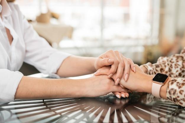 Handen van ondersteunende moeder op die van haar jonge bezorgde of overstuur jonge dochter als teken van troost, zorg en steun