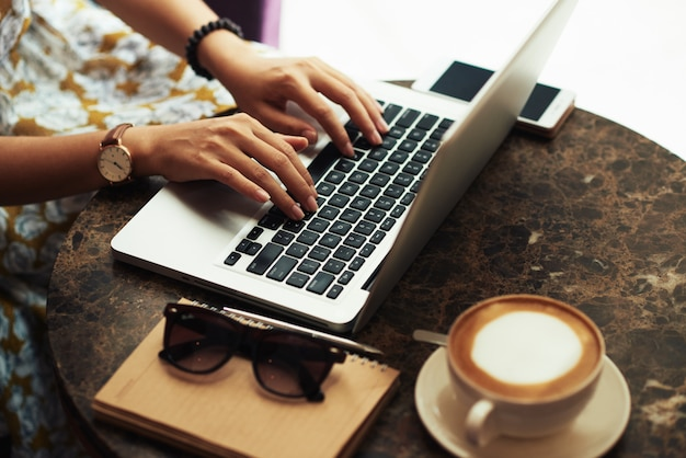 Handen van onherkenbare jonge vrouw die laptop in koffie met behulp van