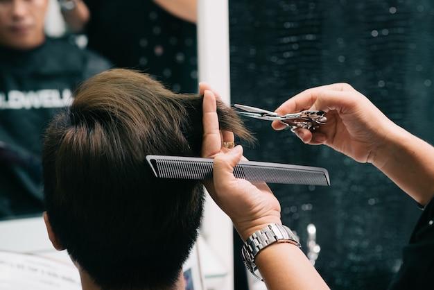 Handen van onherkenbare kapper die het haar van de mannelijke klant in salon snijden