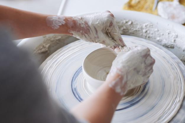Handen van onherkenbare pottenbakker die kleikom op aardewerkwiel maken