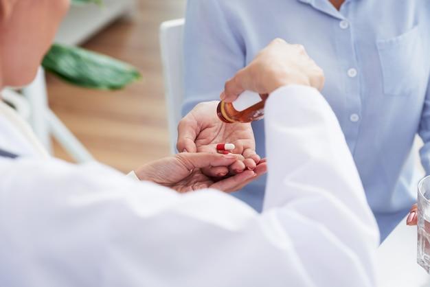 Handen van onherkenbare vrouwelijke arts die pillen geeft aan patiënt