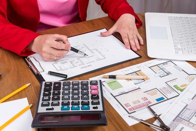 Handen van ontwerper en huisplan, nieuwe projectontwikkeling