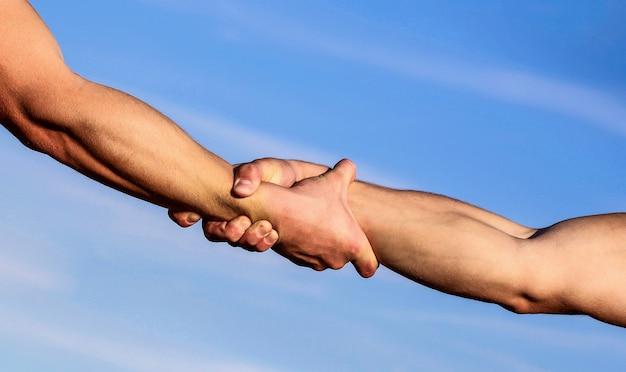 Handen van op blauwe hemelachtergrond. helpende hand concept en internationale dag van vrede, ondersteuning.