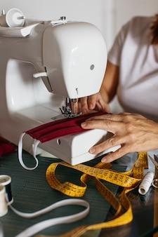 Handen van oude gezichtsmaskers van de vrouwen naaiende doek voor vrienden