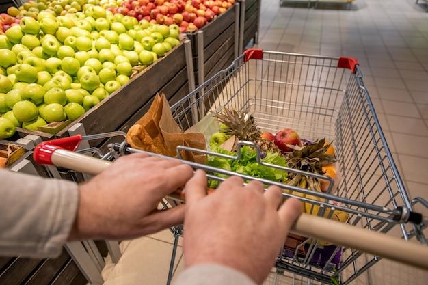Handen van oude mannelijke klant winkelwagentje met voedingsproducten duwen terwijl u langs fruitvertoning met verse appels in supermarkt beweegt