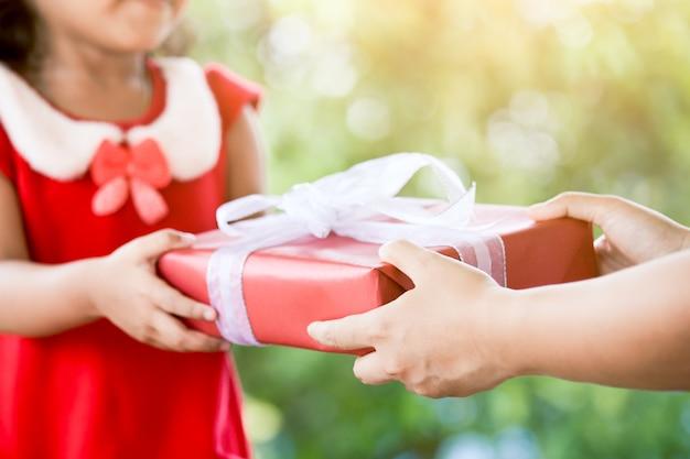 Handen van ouder die kerstmisgift geeft aan kindmeisje