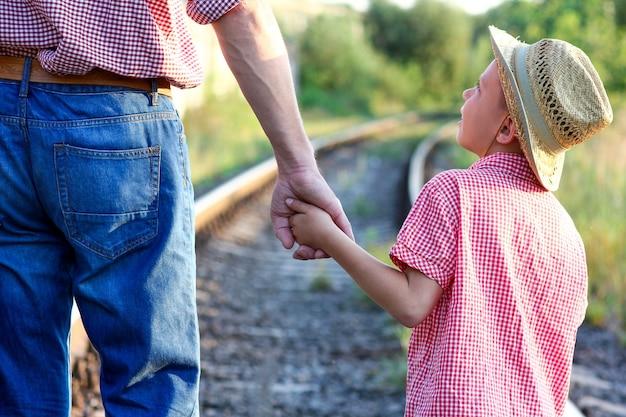Handen van ouder en zoon in cowboyhoed bij de spoorweg met koffer