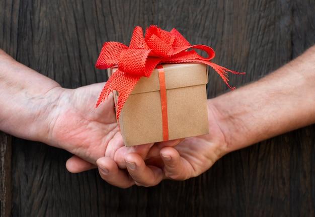Handen van oudere mannen en vrouwen houden de geschenkdoos vast. gepensioneerden overhandigen een geschenk