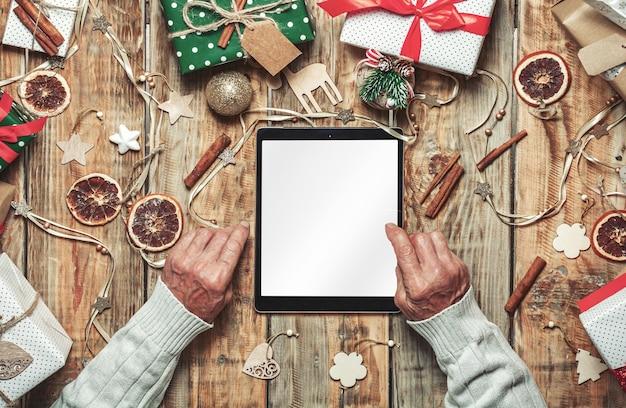 Handen van oudere senior met tablet