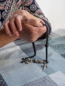 Handen van oudere vrouw bidden met rozenkrans en een kruisbeeld in de gekoppelde handen. concept van het christendom