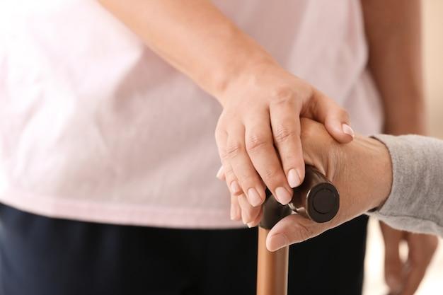 Handen van oudere vrouw en haar kleindochter, close-up. concept van zorg en ondersteuning