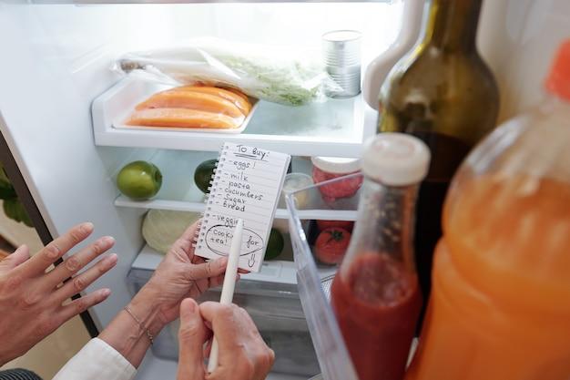 Handen van oudere vrouw en haar volwassen zoon die boodschappenlijstje schrijven bij het controleren van de koelkast
