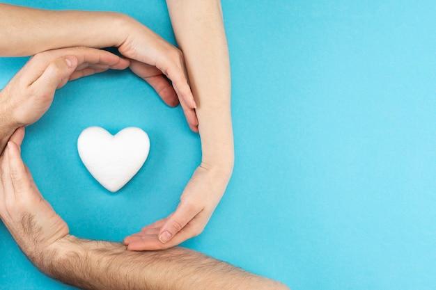 Handen van ouders en een kind omringen een wit hart op een blauwe achtergrond