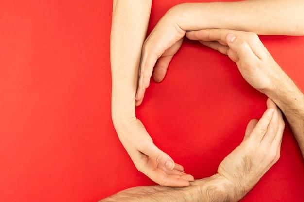 Handen van ouders en kind zijn verzameld in een cirkel met een plek voor tekst in het midden op een rode achtergrond.