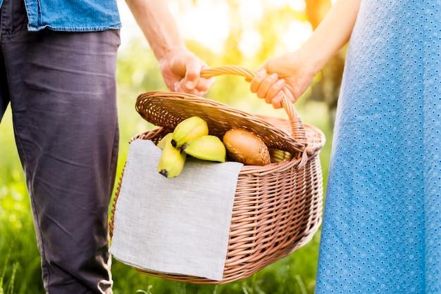 Handen van paar die picknickmandhoogtepunt van voedsel houden