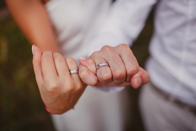 Handen van pasgetrouwden die elkaars pink vasthouden. trouwringen aan je handen