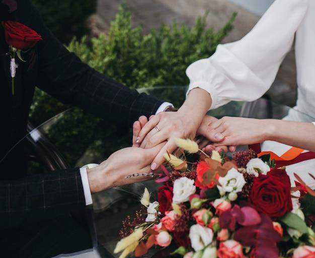 Handen van pasgetrouwden met gouden ringen en bruidsboeket