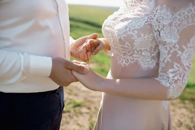 Handen van pasgetrouwden met trouwringen