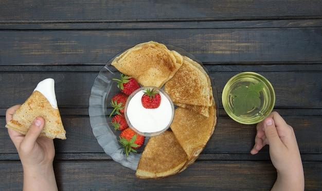 Handen van persoon die eten ontbijt op donkere houten tafel met plaat van pannenkoeken en schotel van room en aardbeien