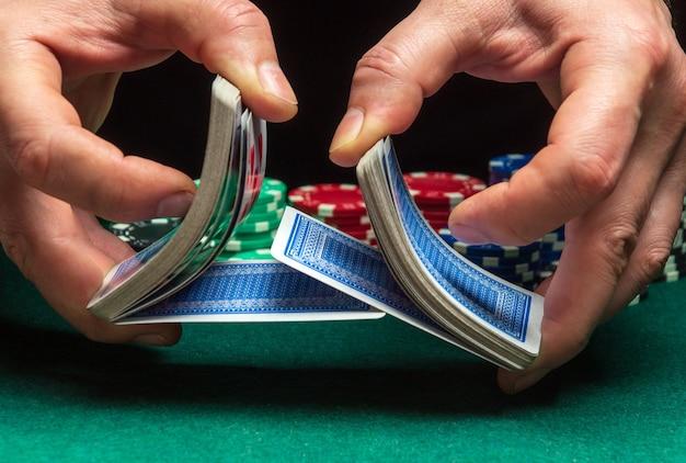 Handen van persoonlijke dealer of croupier die pokerkaarten schudt in pokerclub op de achtergrond van de tafel