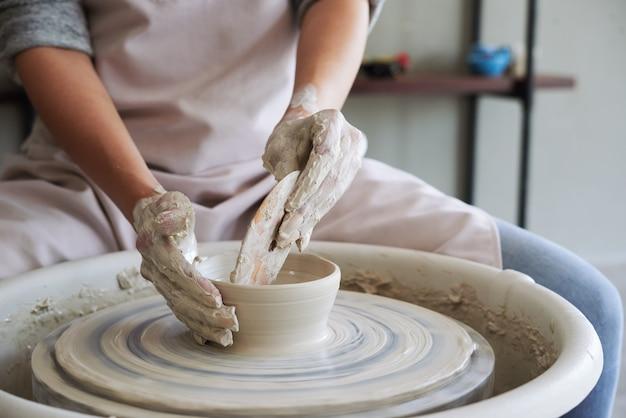 Handen van pottenbakker die houten rib gebruikt om het koppel op de pot waar ze aan werkt te verminderen
