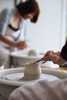 Handen van pottenbakker die overtollige klei afsnijden van pot die ze maakte met draadgereedschap
