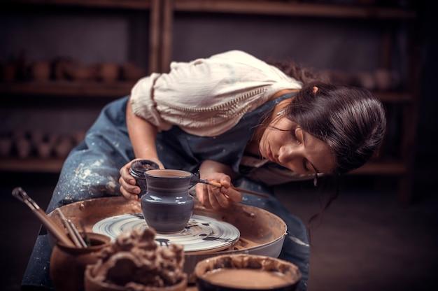 Handen van pottenbakker doen een aarden pot.