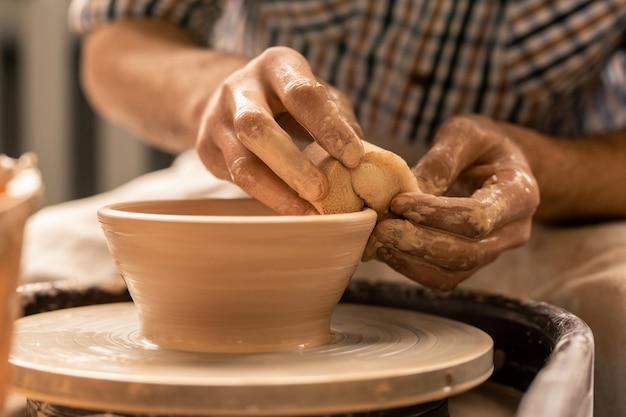 Handen van pottenbakker nemen overtollige klei van de rand van de ruwe pot tijdens het werken door het aardewerkwiel te draaien
