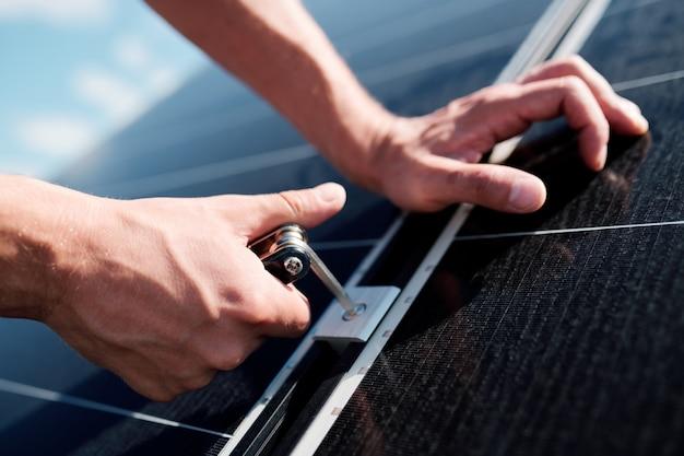 Handen van professionele technicus of ingenieur met behulp van schroef tijdens het installeren van zonnepanelen op het dak van het huis