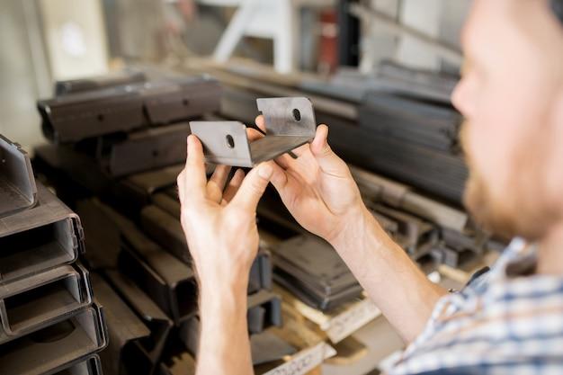 Handen van professionele technisch ingenieur met reserveonderdeel gemaakt van roestvrij staal in fabriek of servicecentrum