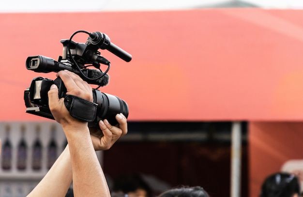 Handen van professionele videocameramexploitant die met zijn materiaal bij nachtgebeurtenis werken.