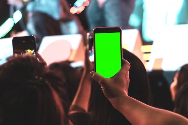 Handen van publiek menigte mensen nemen foto met mobiele smartphone met groen scherm in party concert.