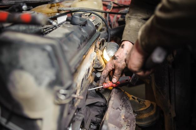 Handen van reparateur monteur bezig met motor met behulp van gereedschap