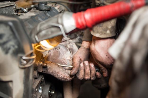 Handen van reparateurmonteur die aan motor werkt die hulpmiddel gebruikt