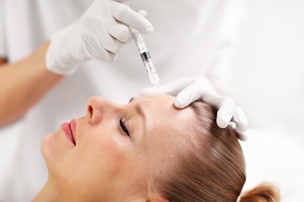 Handen van schoonheidsspecialist die botox-injectie in vrouwelijk voorhoofd maakt