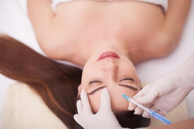 Handen van schoonheidsspecialist die injectie in gezicht, lippen maken. jonge vrouw krijgt schoonheid gezichtsinjecties in salon. gezichtsveroudering, verjonging en hydratatieprocedures. esthetische cosmetologie. detailopname.