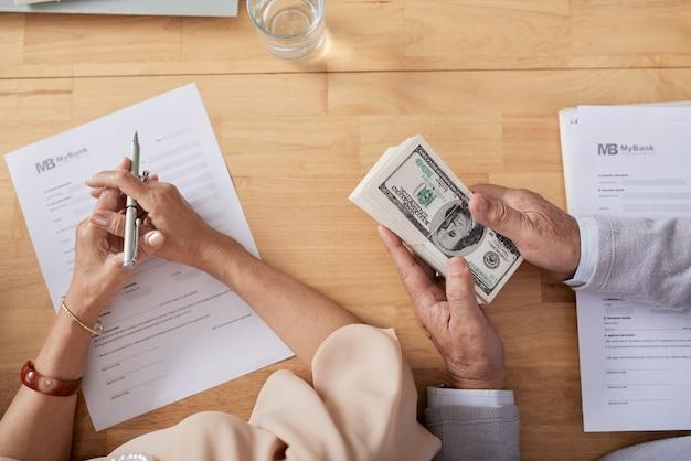 Handen van senior koppel die het formulier van de verkoopakte invullen en contant betalen voor een nieuw huis