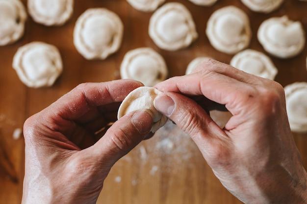 Handen van senior man koken en vormen van kleine zelfgemaakte ongekookte dumplings met vlees op keukentafel. bovenaanzicht