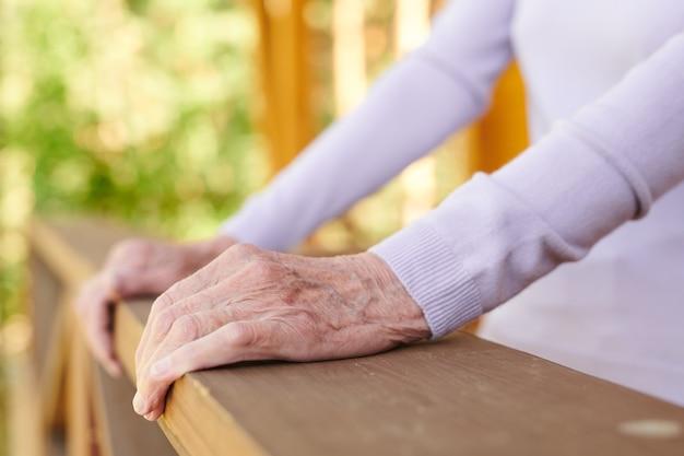 Handen van senior vrouw in witte pullover met lange mouwen vasthouden door houten leuningen van haar landhuis tijdens ontspannen